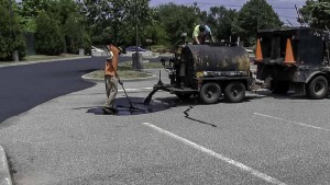 Mixing sealer for parking lot sealcoating in North Amityville, New York.